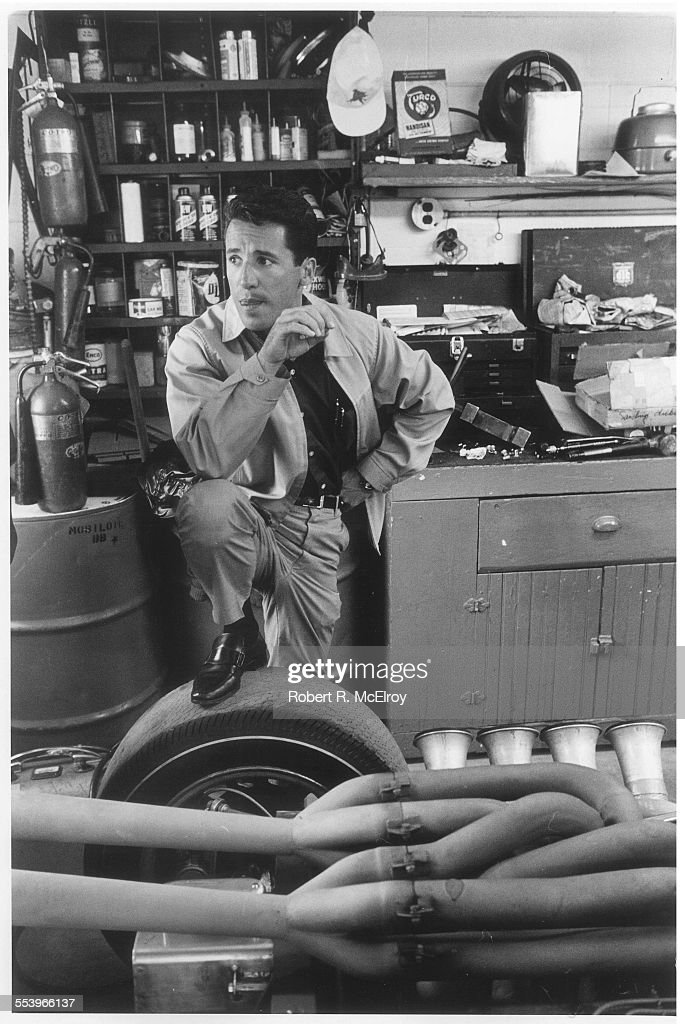 Italianborn American race car driver Mario Andretti stands in a garage on leg on the tire of a car May 1967