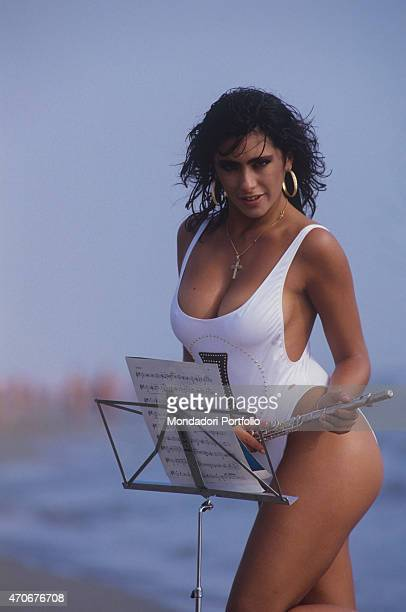Italianborn British singer and showgirl Sabrina Salerno posing in swimsuit holding a flute 1988