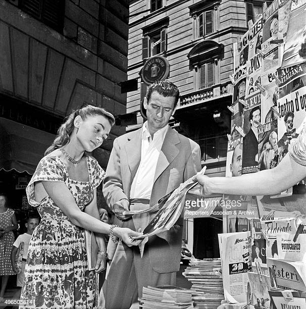 Italianborn French actor and singer Yves Montand stopping to look at some newspapers at a newsstand of via Veneto with French actress Danièle...
