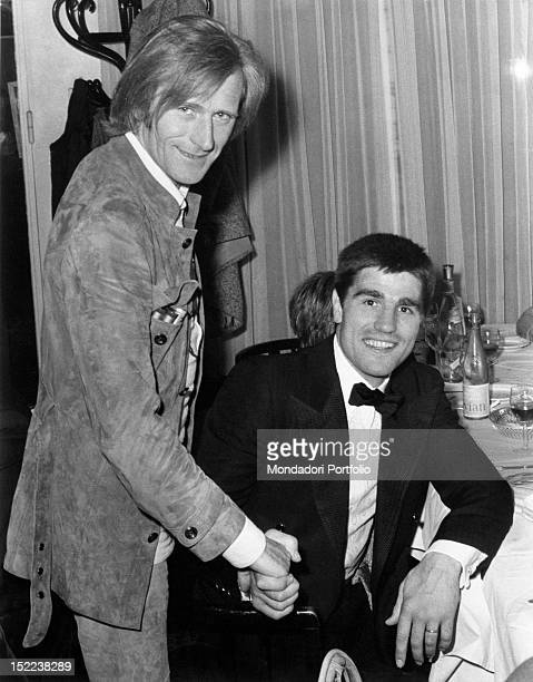 Italianborn French singer and jazz player Nino Ferrer shaking hands with Italian boxer Nino Benvenuti during a party Monte Carlo 1970s
