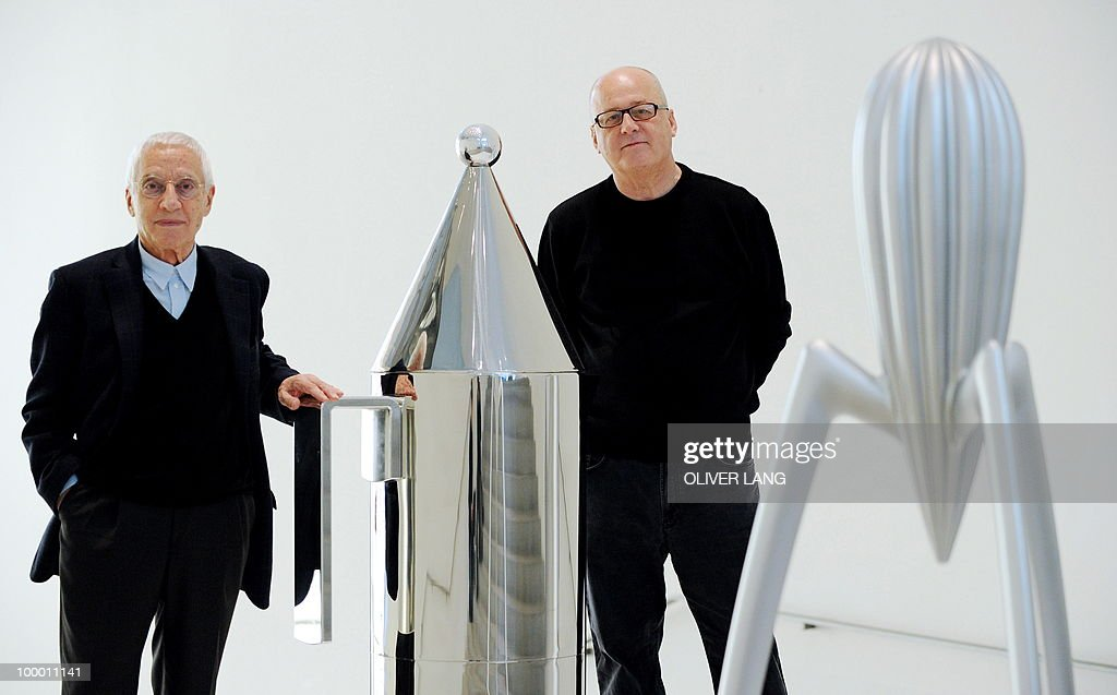 Italians Alberto Alessi (R), owner of the kitchen utensil company Alessi, and designer Alessandro Mendini pose between giant mockups of their kitchen utensils during a press preview of the exhibition 'Oggetti e Progetti - Alessi: storia e futuro di una fabbrica del design italiano' on May 20, 2010 at the Neue Sammlung (New Collection) museum in Munich, southern Germany. From May 22 to September 19, 2010, the museum presents a retrospective of the last 30 years of Italian design, focusing on a key player in the design world: the Alessi company.