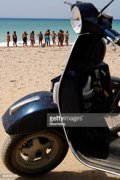 Italians visit the beach near a parked Piaggio Vespa motor scooter in Ribera Sicily Italy Thursday Aug 23 2007