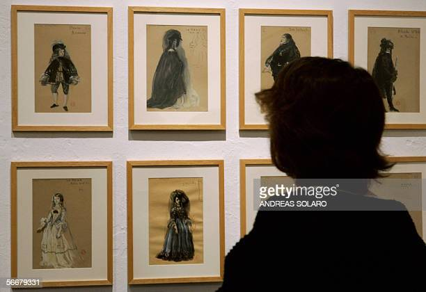 A visitor looks at costumes sketch during an exhibition of theatre and cinema costumes created by italian artists Luciano Damiani Lila de Nobili and...