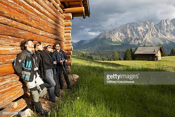 Italy, Alto Adige, Dolomites, Latemar, four friends standing by cabin