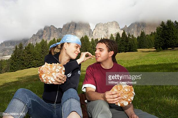 Italy, Alto Adige, young couple sitting in valley eating bread