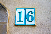 An antique blue and white ceramic number 16 address tile on old pink wall. Shot in Italy. Copy space available.
