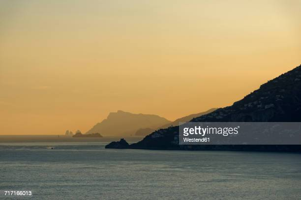 Italy, Campania, sunset at Amalfi coast with rocks of Capri