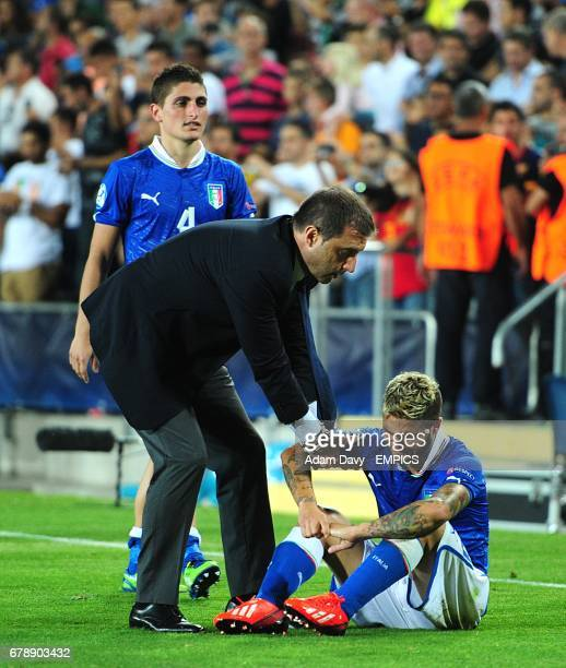 Italy coach Devis Mangia helps Lorenzo Insigne to his feet as he sits dejected after the final whistle
