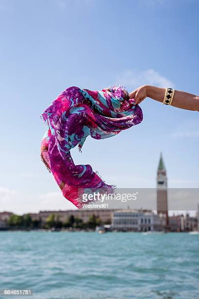 Italy, female tourist waving with cloth in Venice