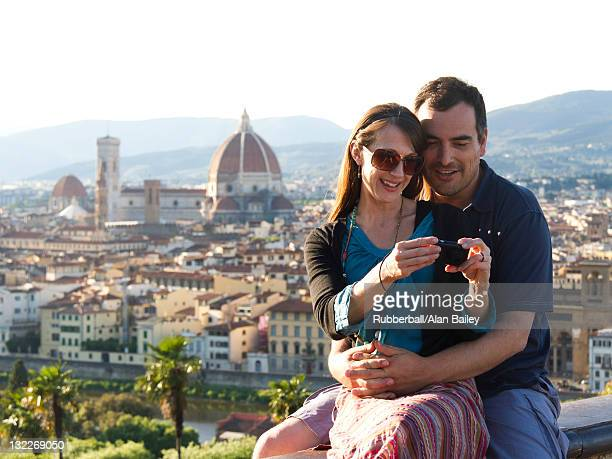 Italy, Florence, Couple photographing self with townscape in background
