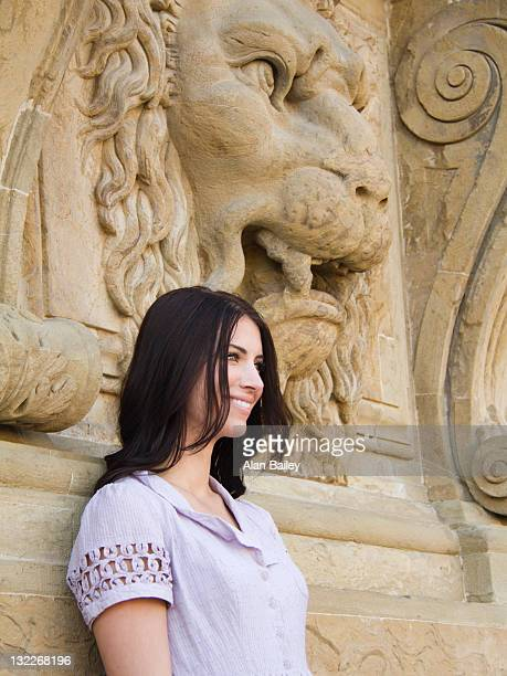 Italy, Florence, Portrait of young attractive woman with lion sculpture in background