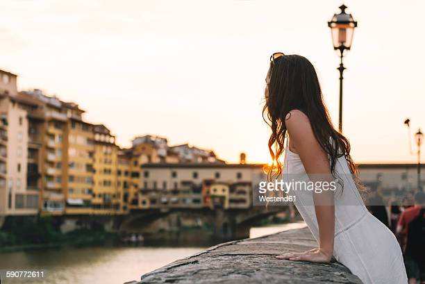 Italy, Florence, woman watching sunset behind Ponte Vecchio