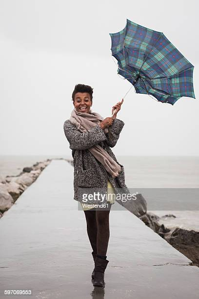 Italy, Grado, woman holding umbrella on a rainy day in front of the sea