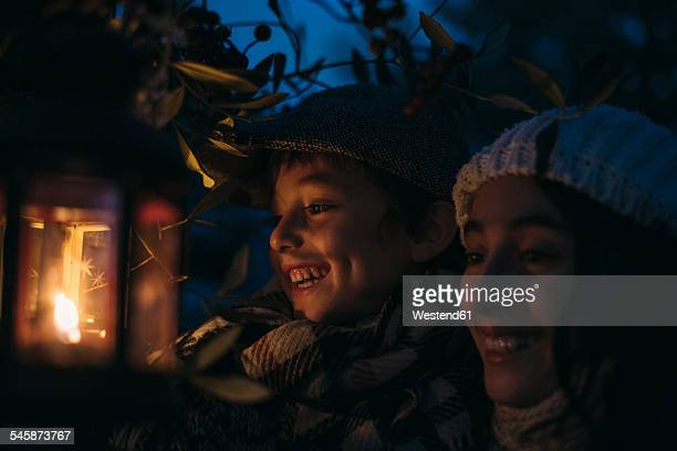 Italy, Grosseto, laughing siblings with lighted Christmas lantern by night