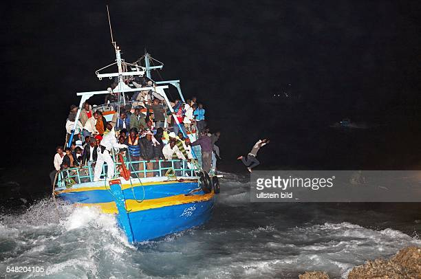 Italy Havarie of an overloaded boat with refugee boat at the coast of Lampedusa Refugees are jumping into the sea