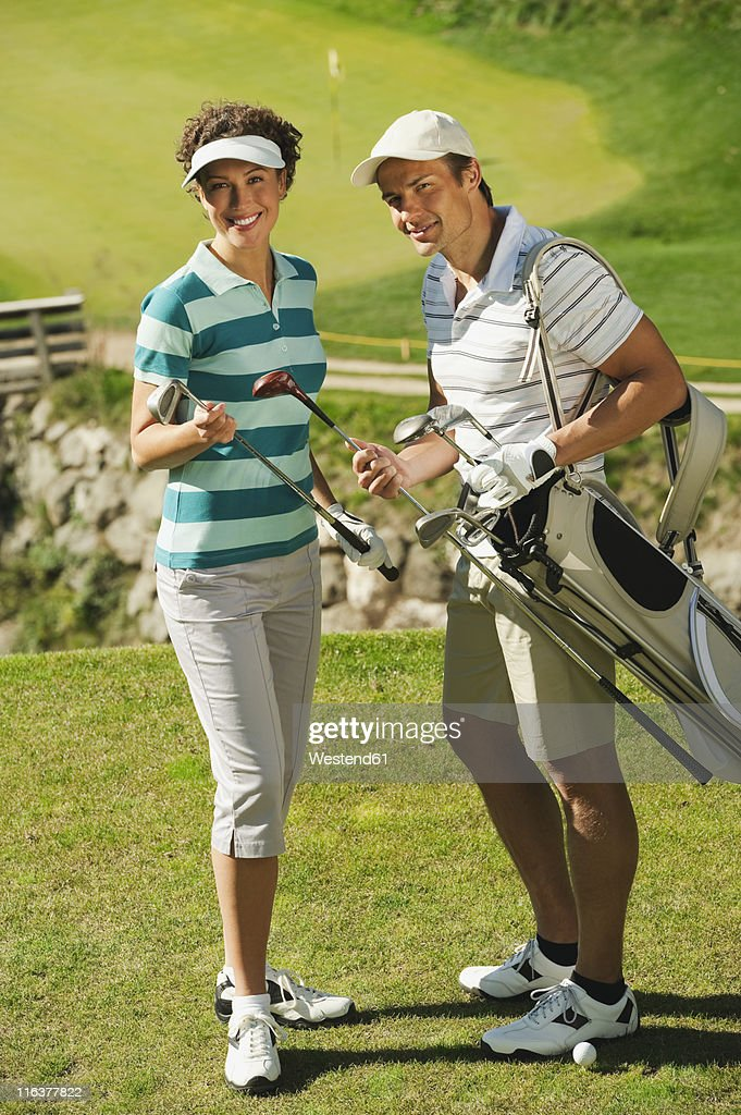 Italy, Kastelruth, Golfers on golf course, smiling, portrait : Stock Photo
