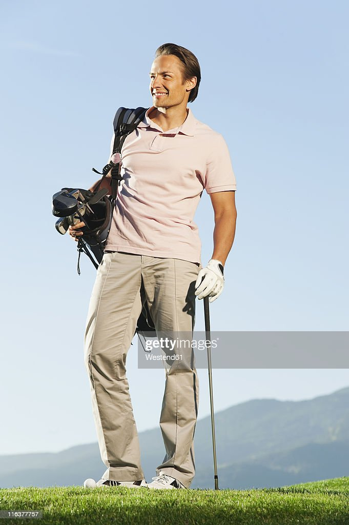 Italy, Kastelruth, Mid adult man with golf bag on golf course : Stock Photo
