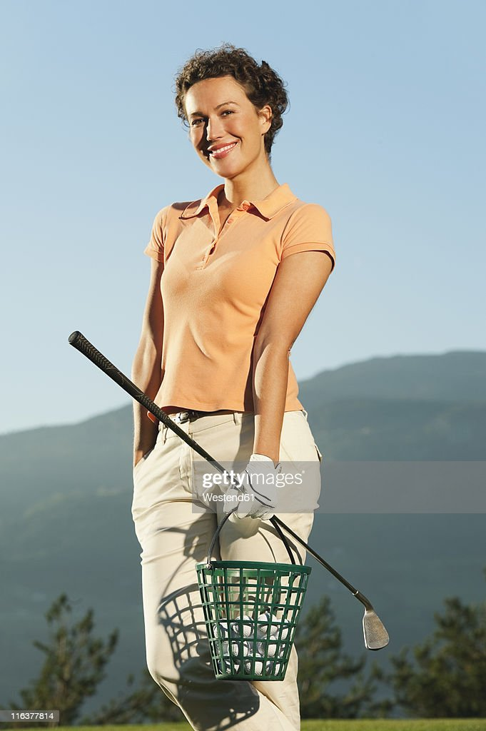 Italy, Kastelruth, Mid adult woman holding basket and golf club, portrait : Stock Photo