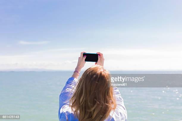 Italy, Lignano Sabbiadoro, woman with smartphone, selfie