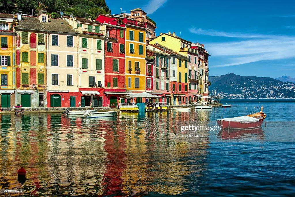 Italy, Liguria, Geneva, Portofino, Multicolored waterfront houses and harbor with anchored motor boats