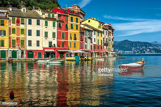 Italy, Liguria, Geneva, Portofino, Multicolored waterfront houses and harbor with anchored motor boats