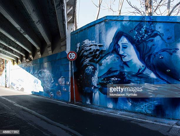 Italy Lombardy Milan Whole Artwork View Mural painting painted in different light of blue representing the smiling face of a young woman rising from...