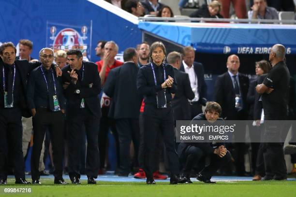 Italy manager Antonio Conte crouches on the touchline as he watches the penalty shootout