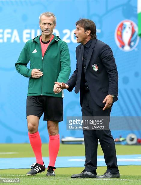 Italy manager Antonio Conte stands next to fourth official Martin Atkinson as he argues with the officials on the touchline