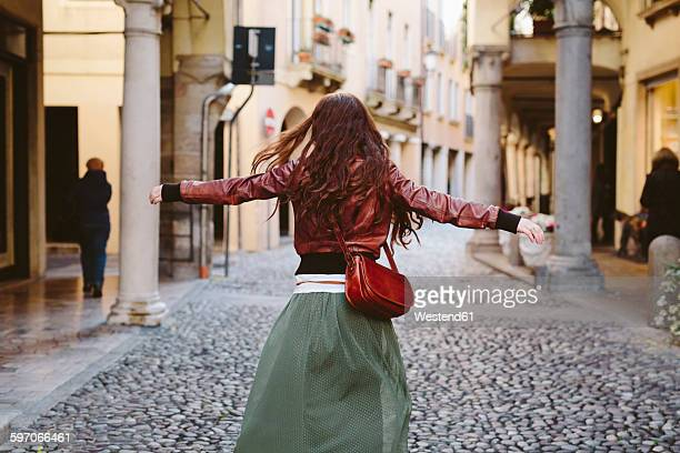 Italy, Padua, woman walking with outstretched arms in an alley