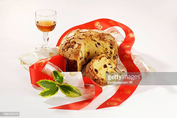 Italy, Panettone and glass of vin santo on white background