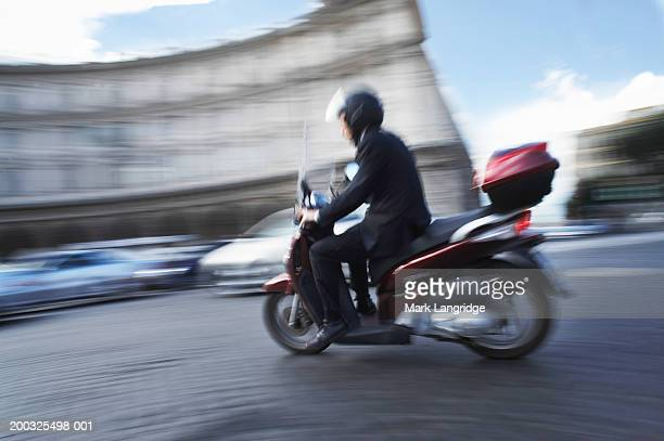 Italy, Rome, man riding motorbike, side view (blurred motion)