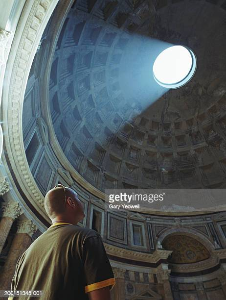 Italy, Rome, The Pantheon, man looking domed ceiling