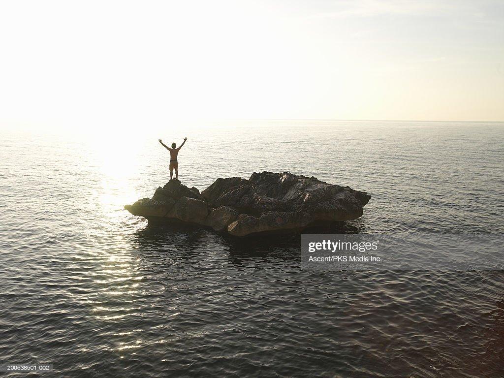Italy, Sardinia, Cala Gonone, man standing on island, arms raised : Stock Photo