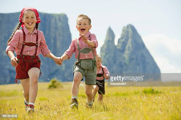 Italy, Seiseralm, Children (4-9) running through meadow