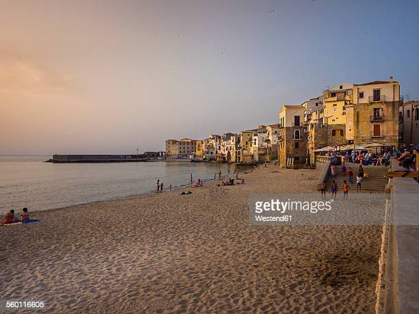Italy, Sicily, Cefalu, view to medieval houses with beach in the foreground at evening twilight