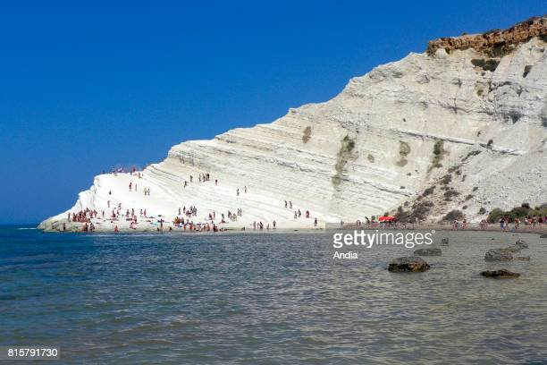 on the south coast near Sciacca a few kilometers west of Agrigento tourists in the creek at the bottom of the limestone cliff of La Scala dei Turchi...