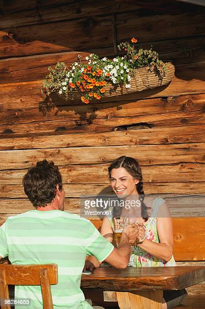 Italy, South Tyrol, Couple sitting on bench toasting beer glass, smiling