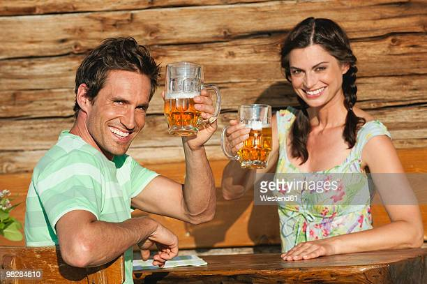 Italy, South Tyrol, Couple sitting on bench holding beer glass, smiling, portrait