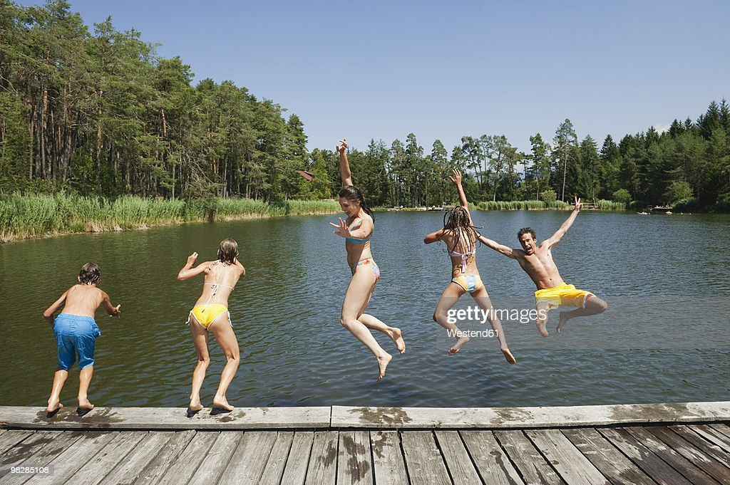 Italy, South Tyrol, Parents with children (10-13) jumping into lake : Stock Photo