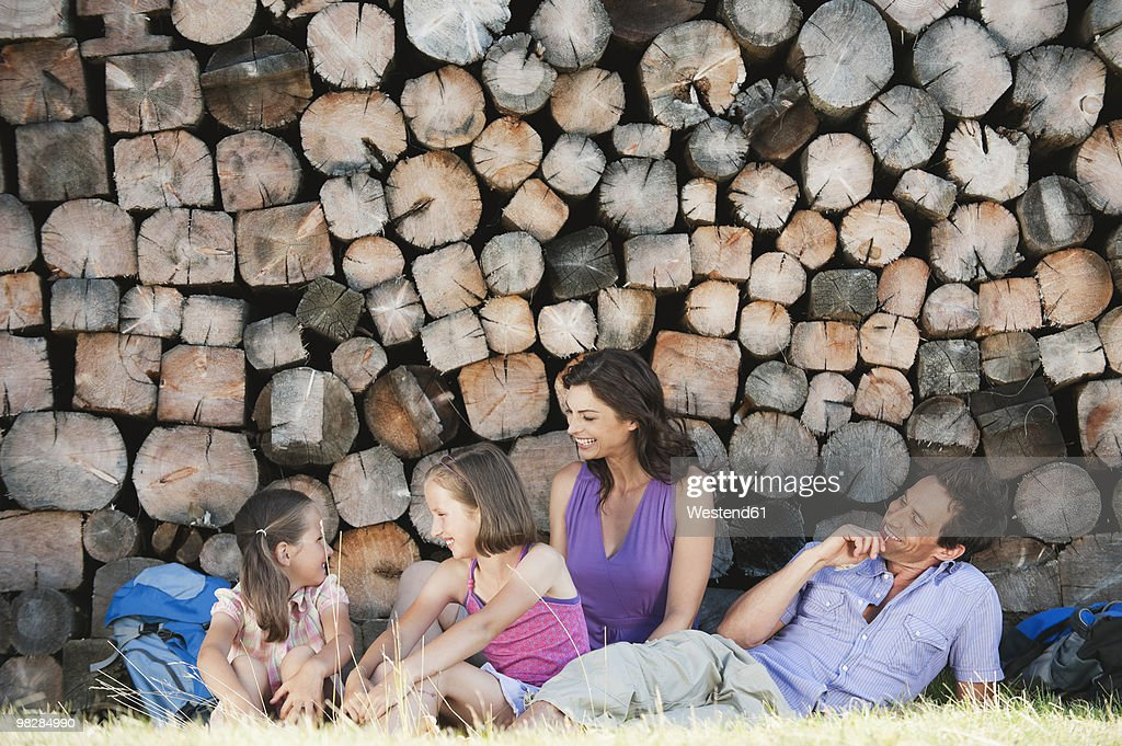Italy, South Tyrol, Parents with children (6-11) sitting against pile of log, smiling : Stock Photo