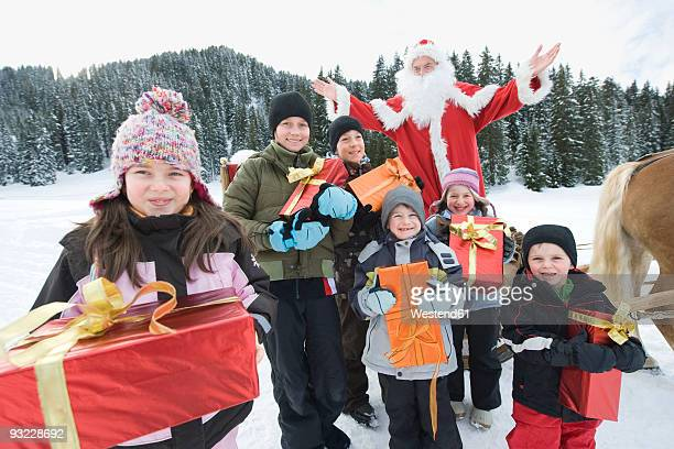 Italy, South Tyrol, Seiseralm, Children (2-13) holding gift boxes, Santa Claus in background, portrait