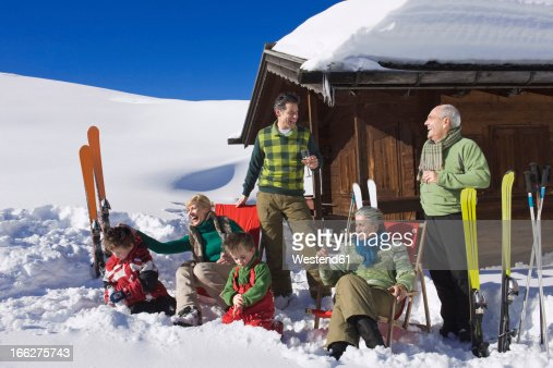 Italy, South Tyrol, Seiseralm, Three-generation family with two boys (4-5) in front of log cabin with ski gear