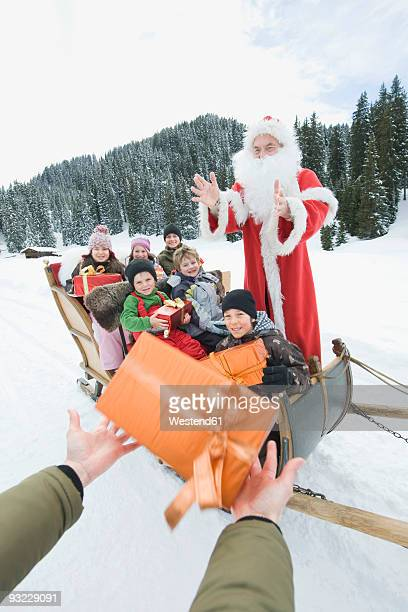 Italy, South Tyrol, Seiseralm, Santa Claus and children (2-13), children holding gift boxes
