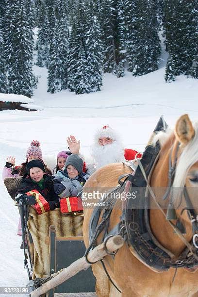 Italy, South Tyrol, Seiseralm, Santa Claus and children (2-9) sitting in sleigh, smiling