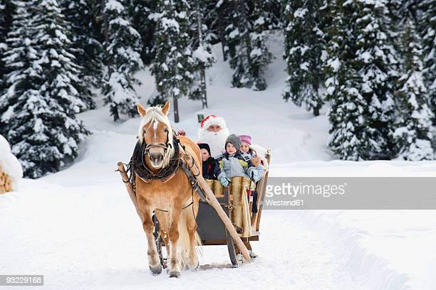 Italy, South Tyrol, Seiseralm, Santa Claus and children (2-9) sitting in sleigh