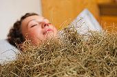 Italy, South Tyrol, Woman having hay bath in hotel urthaler