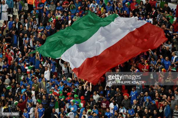 Italy supporters hold up a huge Italian flag during the opening ceremony prior to the start of the Euro 2016 group E football match between Belgium...