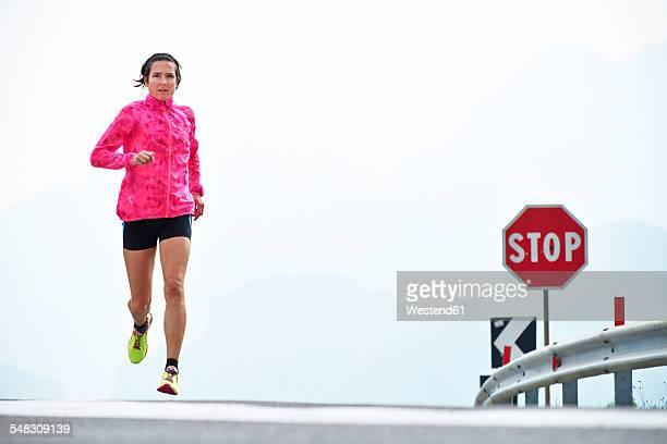Italy, Trentino, woman running on road near Lake Garda