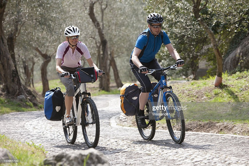 Italy, Trento, Man and woman cycling through country road