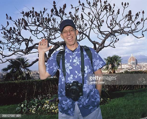 Italy, Tuscany, Florence, male tourist waving, portrait